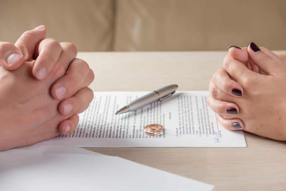 folded hands and wedding rings on divorce papers