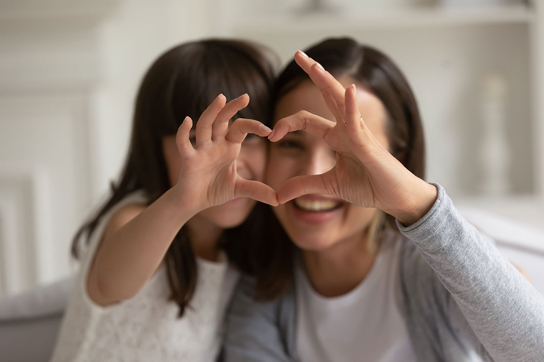 mother and daughter making heart with hands