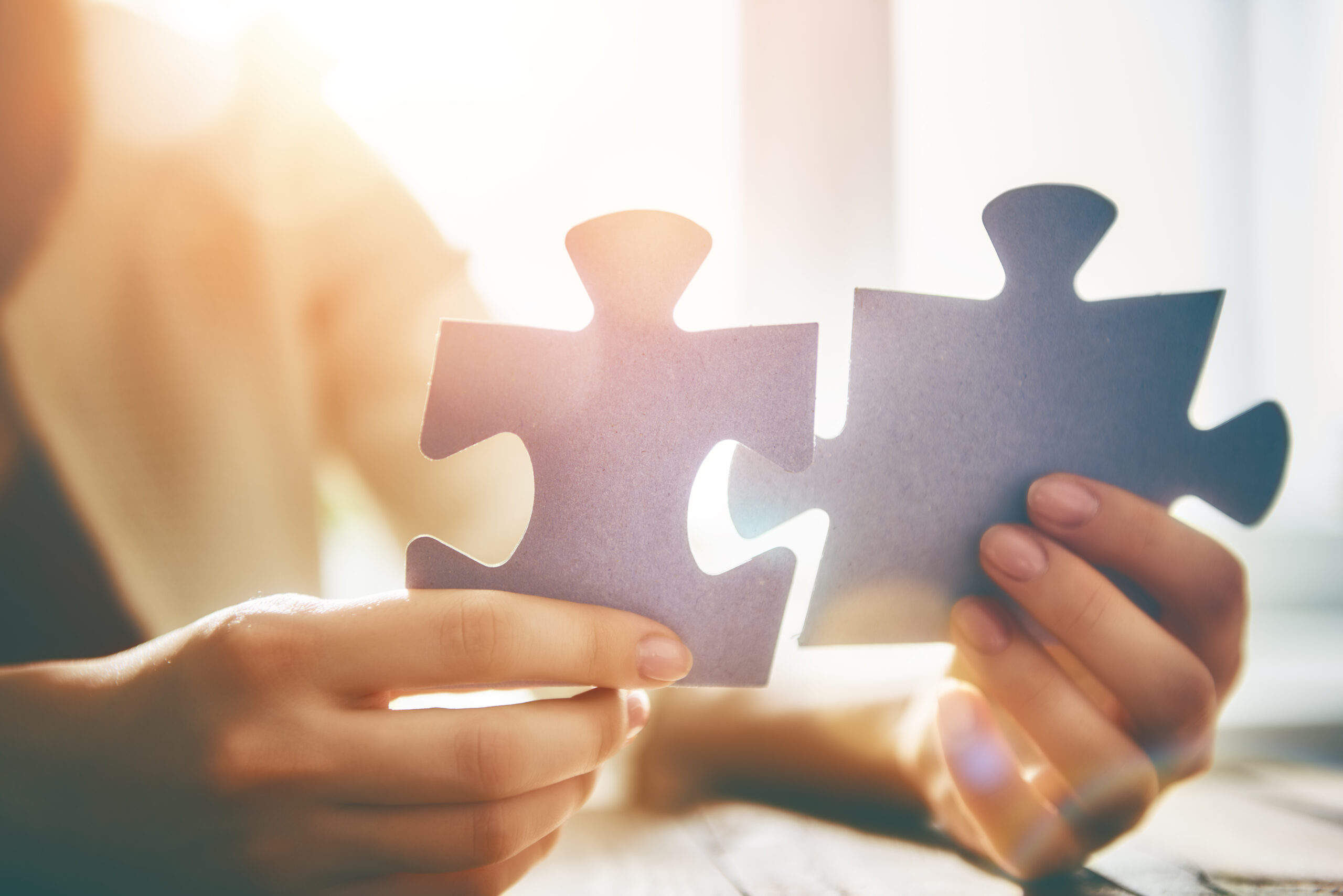 woman connecting two large puzzle pieces
